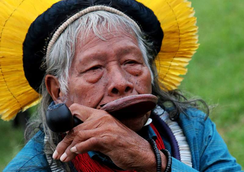 FILE - In this Aug. 26, 2019 file photo, Kayapo tribal leader Raoni Metuktire smokes a pipe after a press conference in Bidart, southwestern France. The Indigenous leader emblematic of the fight for the preservation of the Amazon forest in Brazil was hospitalized with symptoms of pneumonia and tested positive for COVID-19, according to the Raoni Institute on Monday, Aug. 31, 2020. (AP Photo/Bob Edme, File)