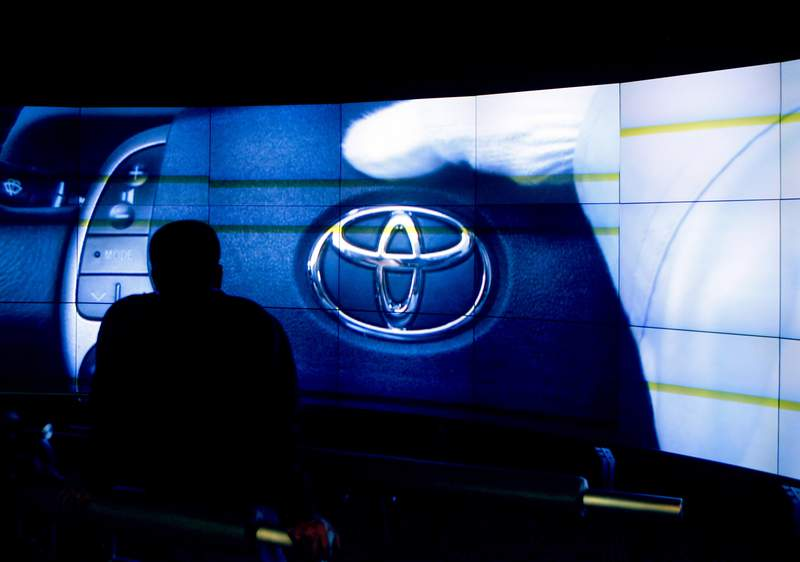 A Toyota corporate logo appears on a screen as a visitor watches a video showing the assembly line procedures of a Toyota Motor Corp.'s plant at the automaker's exhibition hall in Toyota, central Japan, Thursday, March 4, 2010. Toyota says it will roll out two new battery-electric vehicles and one plug-in gas-electric hybrid in the U.S. this year as the parade of new EVs continues. The company gave few specifics on the vehicles during a presentation Wednesday, Feb. 10, 2021 but said one electric vehicle would be an SUV.(AP Photo/Shuji Kajiyama, file)