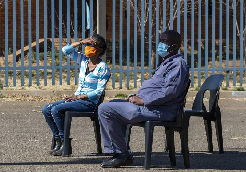 People wearing face masks to protect against coronavirus, sit on chairs whilst queuing to be screened and tested for COVID-19 in Eldorado Park outside of Johannesburg, South Africa, Monday, Aug. 3, 2020. (AP Photo/Themba Hadebe)