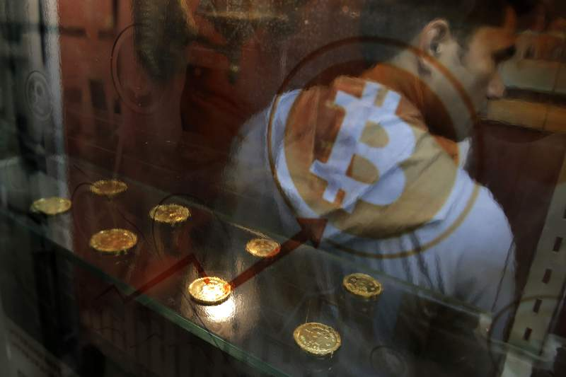 FILE- In this Dec. 8, 2017, file photo, a man uses a Bitcoin ATM.  (AP Photo/Kin Cheung, File)
