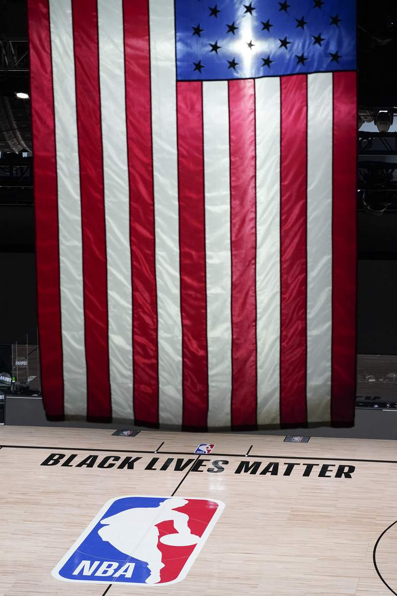 Black Lives Matter is displayed near the NBA logo in an empty basketball arena Friday, Aug. 28, 2020, in Lake Buena Vista, Fla. The NBA playoffs will resume Saturday after the league and the National Basketball Players Association detailed the commitments that made players comfortable continuing the postseason. In a joint statement released Friday, the sides say they will immediately establish a social justice coalition, made up of players, coaches and owners, that would focus on issues such as voting access and advocating for meaningful police and criminal justice reform. (AP Photo/Ashley Landis, Pool)