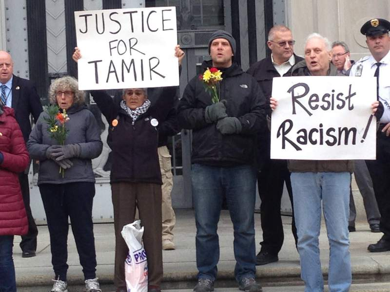 "In this 2016 photo, Martin Gugino, right, holds a sign reading ""Resist Racism,"" in Washington, D.C., as part of a protest over the 2014 killing of 12 year-old African American Tamir Rice in Cleveland.  Gugino and others demanded murder charges against police officers for the killing. (Mark Colville via AP)"
