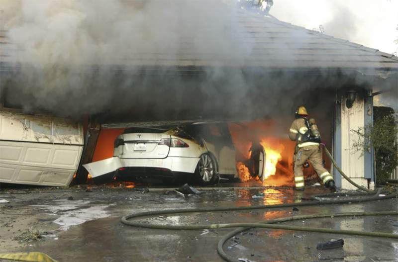 This undated photo provided by National Transportation Safety Board, The Orange County Fire Authority battles a fire on a burning vehicle inside a garage in Orange County, Calif.  When firefighters removed the SUV from the garage to assess the fire , they identified the fuel source as the SUVs high-voltage battery pack.  U.S. safety investigators say electric vehicle fires pose risks to first responders, and manufacturers have inadequate guidelines to keep them safe. (Orange County Sheriffs Department/National Transportation Safety Board via AP)