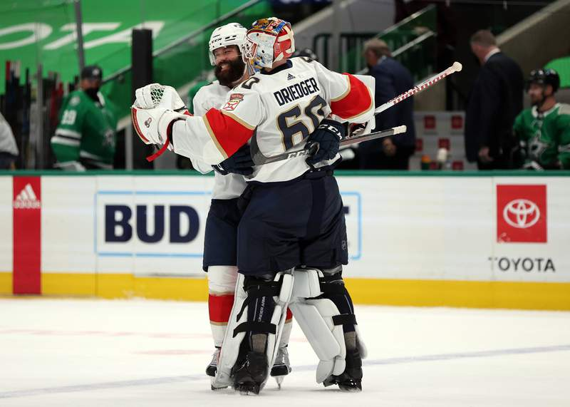 Radko Gudas and Chris Driedger of the Florida Panthers celebrate a 3-2 win against the Dallas Stars in overtime at American Airlines Center on April 13, 2021 in Dallas, Texas.