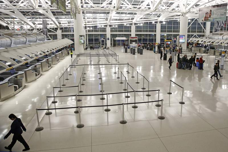 People visit an international terminal at John F. Kennedy airport, Friday, March 13, 2020, in New York. A ban on travelers from most European countries begins at midnight Friday, and travelers returning from there will be screened. The ban is the latest calamity for a global travel industry already reeling from falling bookings and canceled reservations as people try to avoid contracting and spreading the coronavirus. (AP Photo/Kathy Willens)