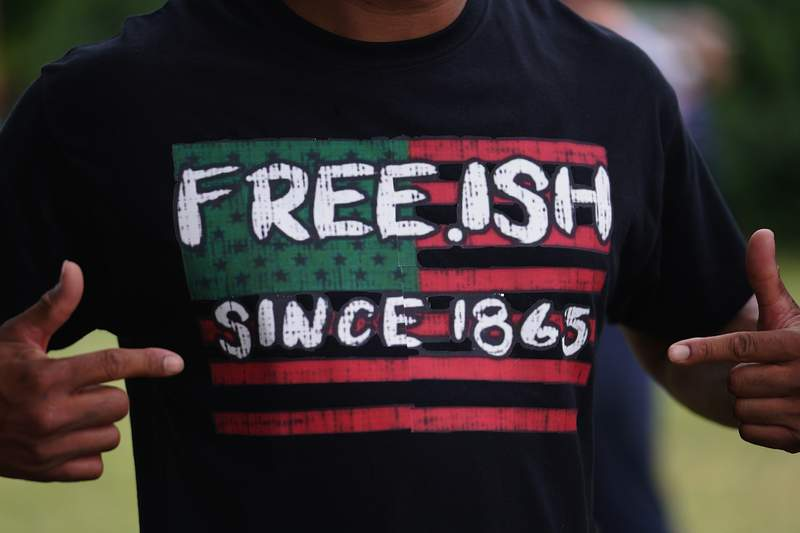 A man displays a shirt celebrating the freedom of enslaved Black people during a Juneteenth celebration on June 19, 2020 in Tulsa, Oklahoma. Juneteenth commemorates June 19, 1865, when a Union general read orders in Galveston, Texas stating all enslaved people in Texas were free, according to federal law.