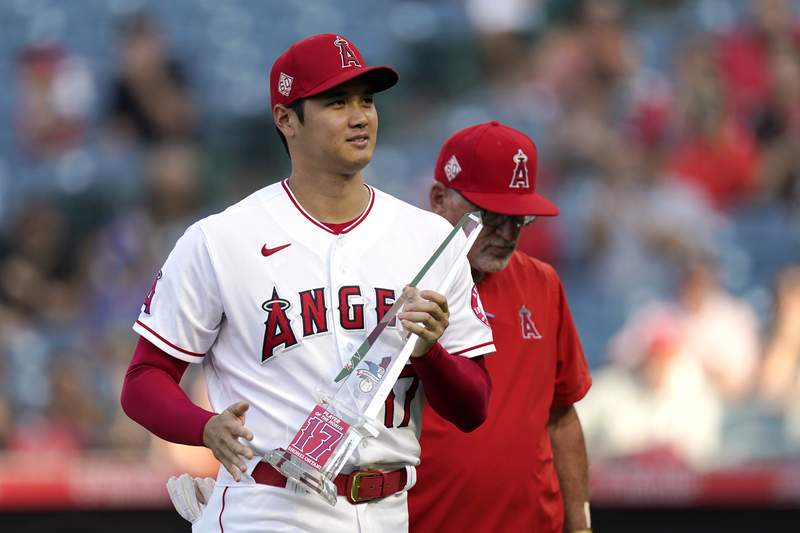 Los Angeles Angels designated hitter Shohei Ohtani holds his American League Player of the Month trophy after being presented with it prior to a baseball game against the Seattle Mariners Friday, July 16, 2021, in Anaheim, Calif. (AP Photo/Mark J. Terrill)