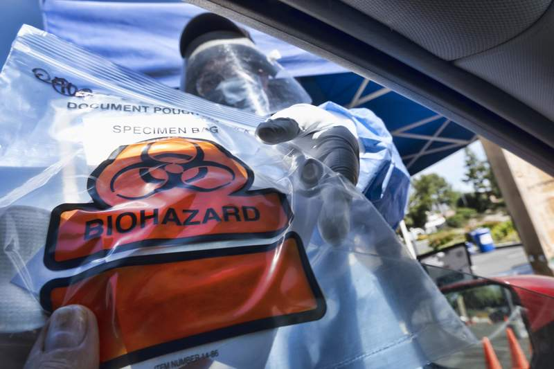 A medical worker hands a self-administered coronavirus test to a patient at a drive-through testing site in this file photo.