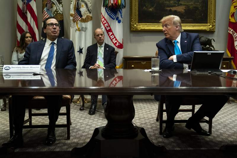 President Donald Trump listens as Treasury Secretary Steven Mnuchin speaks during a conference call with banks on efforts to help small businesses during the coronavirus pandemic, at the White House, Tuesday, April 7, 2020, in Washington. (AP Photo/Evan Vucci)