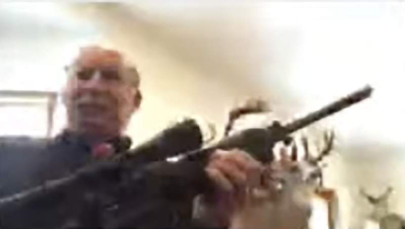 In this screen grab taken from a Zoom meeting provided by the Grand Traverse County Board of Commissioners, Grand Traverse County Commissioner Ron Clous holds a rifle at his home during a county commissioner meeting Wednesday, Jan. 20, 2021, in Michigan. Clous displayed the rifle during the online meeting in response to a citizen's comments about a far-right extremist group, drawing backlash from some local residents. (Grand Traverse County Board of Commissioners via AP)