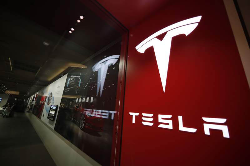 FILE - In this Feb. 9, 2019, file photo, a sign bearing the company logo stands outside a Tesla store in Cherry Creek Mall in Denver. U.S. safety regulators are continuing their investigation into complaints that Teslas giant touch screens can fail and cause the cars to lose the rear camera display and other functions. A preliminary investigation was opened in June 2020 covering 63,000 Model S vehicles. (AP Photo/David Zalubowski, File)