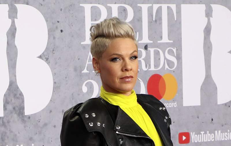 FILE - In Wednesday, Feb. 20, 2019 file photo, singer Pink poses for photographers upon arrival at the Brit Awards in London.  U.S. pop singer Pink has offered to pay a fine given to the Norwegian female beach handball team for wearing shorts instead of the required bikini bottoms. Pink said she was very proud of the team for protesting against the rule that prevented them from wearing shorts like their male counterparts. At the European Beach Handball Championships in Bulgaria last week, Norways female team was fined 1,500 euros ($1,770) for what the European federation called improper clothing and a breach of clothing regulations. (Photo by Vianney Le Caer/Invision/AP, File)