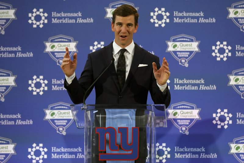 FILE - New York Giants NFL football quarterback Eli Manning announces his retirement in East Rutherford, N.J., in this Friday, Jan. 24, 2020, file photo. Eli Manning has a new job with the New York Giants. The two-time Super Bowl MVP is rejoining the organization to work in business opportunities and fan initiatives. The Giants announced the hiring Monday, June 21, 2021, roughly 18 months after Manning retired following the 2019 season. (AP Photo/Adam Hunger, File)