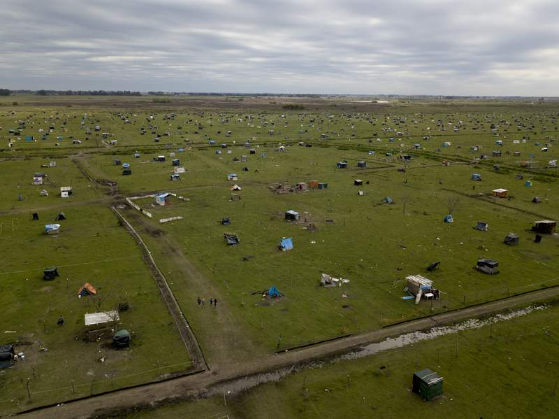 Casas improvisadas creadas por ocupantes ilegales cubren un campo en Guernica, provincia de Buenos Aires, Argentina, el jueves 1 de octubre de 2020. (AP Foto/Natacha Pisarenko)