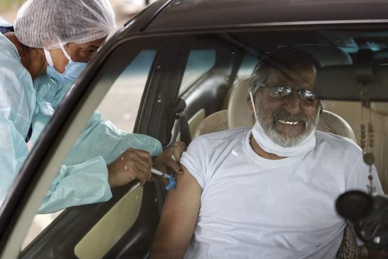 Un hombre recibe una inyeccin de la vacuna de Sinovac en su auto en Brasilia, Brasil, el jueves 11 de marzo de 2021. (AP Foto/Eraldo Peres)