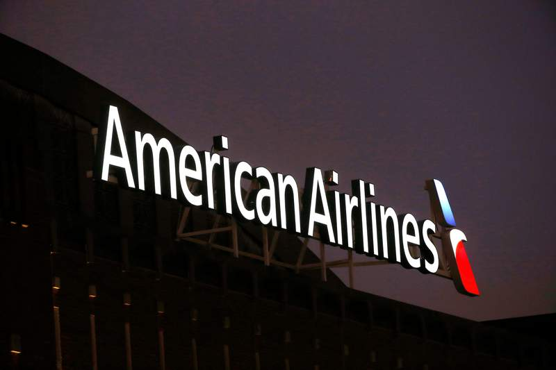 FILE- This Dec. 19, 2017, file photo shows the American Airlines logo on top of the American Airlines Center in Dallas. Airline stocks rose Monday, March 8, 2021 spurred by signs that vaccine rollouts could set up a rebound in travel later this year. (AP Photo/Michael Ainsworth, File)