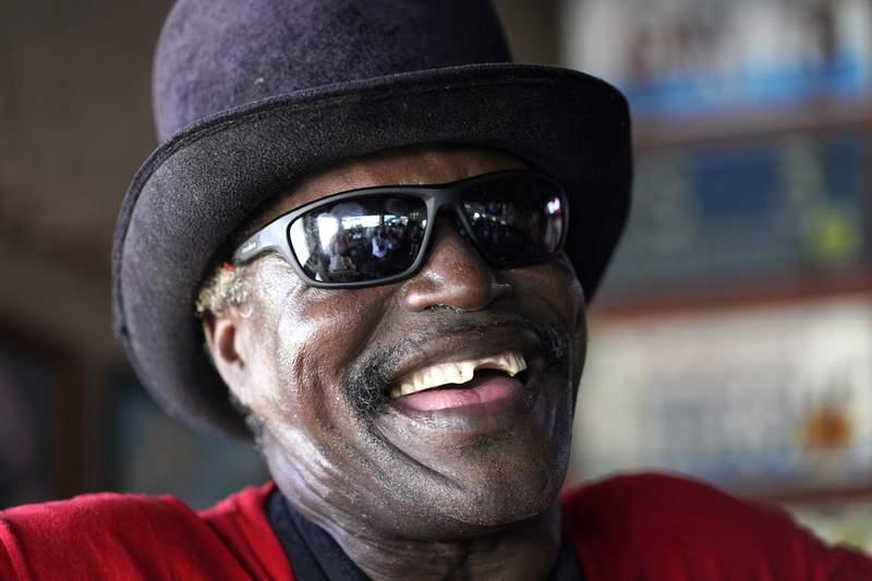 Charles Adams sonre mientras hace una pausa tocando su saxofn en el Elbo Room, en Fort Lauderdale, Florida, el 22 de junio de 2021. Adams vive actualmente en un hotel como parte de un apoyo para personas sin hogar. (AP Foto/Lynne Sladky)