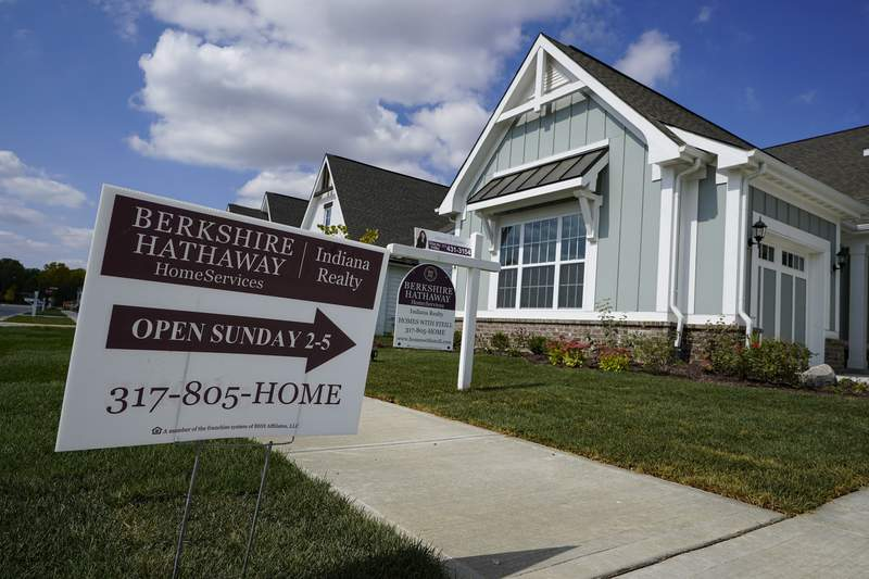 An open house is posted in front of a home for sale in Westfield, Ind., Friday, Sept. 25, 2020. The market for existing homes cooled slightly in November, the National Association of Realtors said Tuesday, Dec. 22, 2020 after climbing through the late spring, summer and early fall despite the pandemic. (AP Photo/Michael Conroy)