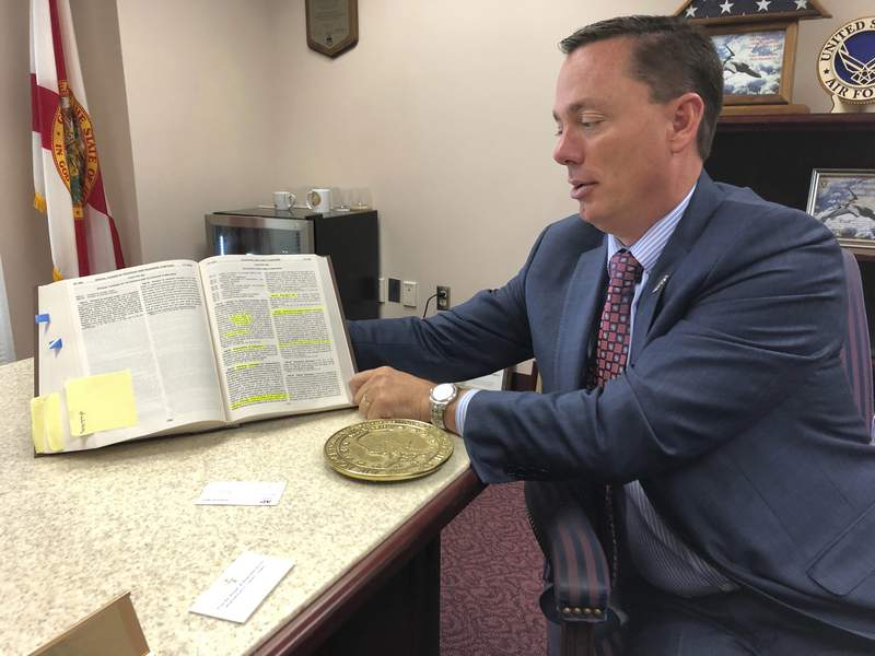 Rep. Tommy Gregory, holds a book of laws that includes antiquated statutes regulating the telegraph industry at his office Wednesday, Jan. 15, 2020, in Tallahassee, Fla. Gregory wants lawmakers to repeal these laws that do not apply to today's telecommunication industry. A state House committee on Wednesday agreed unanimously to repeal Chapter 363 of the Florida Statute in its entirety. (AP Photo/Bobby Calvan)