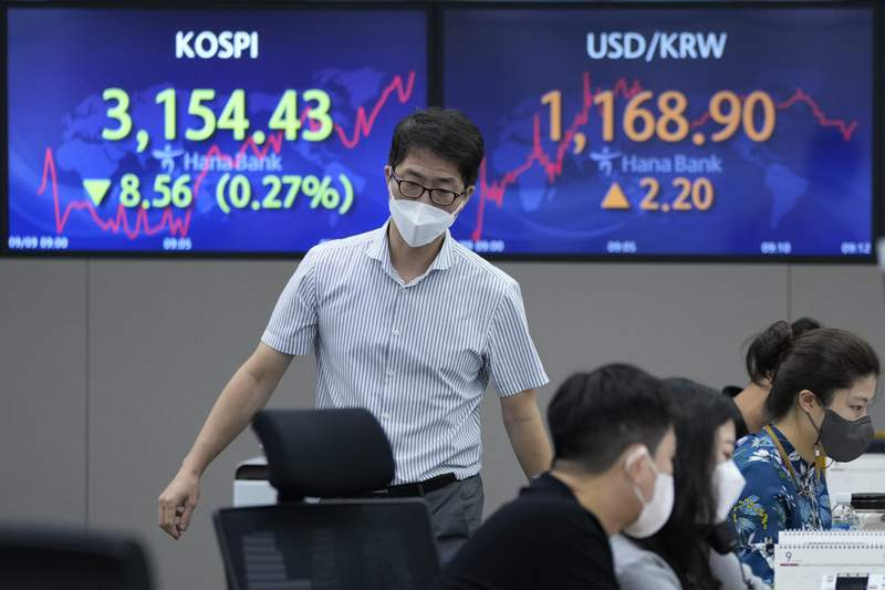 A currency trader passes by screens showing the Korea Composite Stock Price Index (KOSPI), left, and the foreign exchange rate between U.S. dollar and South Korean won at the foreign exchange dealing room of the KEB Hana Bank headquarters in Seoul, South Korea, Thursday, Sept. 9, 2021. Shares fell in Asia on Thursday after further losses on Wall Street following a Federal Reserve report showing U.S. economic activity slowed this summer. (AP Photo/Ahn Young-joon)
