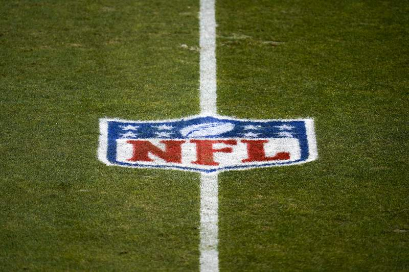 File-This Jan. 3, 2021, file photo shows the NFL logo on the field before a game between the Denver Broncos and the Las Vegas Raiders in Denver. The NFL and NFL Players Association have updated COVID-19 protocols to loosen restrictions for fully vaccinated players and to encourage others to get the vaccine.  Unvaccinated players must continue to get daily testing, wear masks and practice physical distancing. They wont be allowed to eat meals with teammates, cant participate in media or marketing activities while traveling, arent permitted to use the sauna or steam room and may not leave the team hotel or interact with people outside the team while traveling. (AP Photo/Jack Dempsey, File)