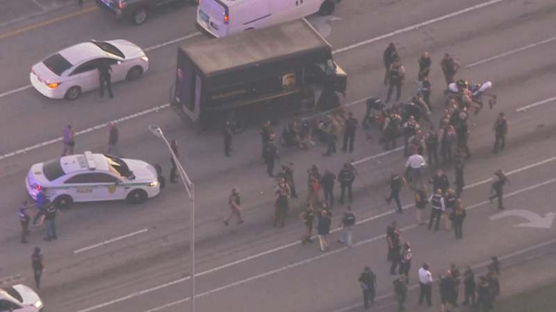 Police surround a UPS truck after a pursuit ends in gunfire.