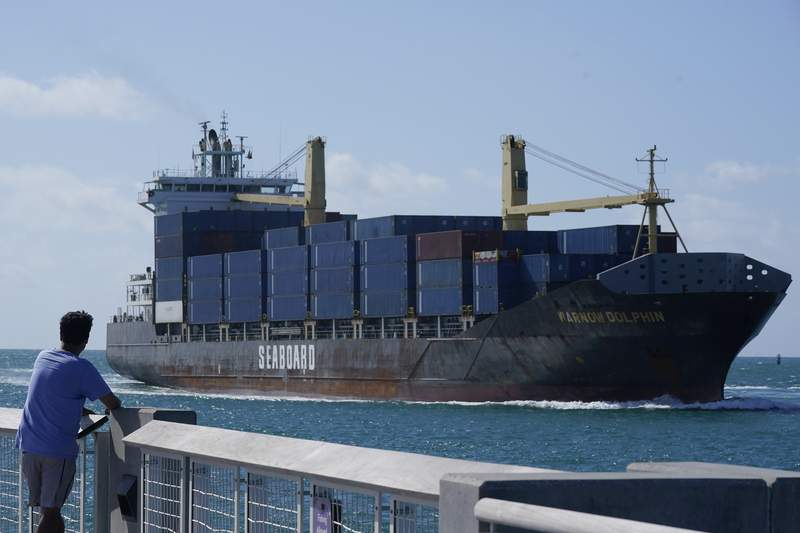 A man watches as the Warnow-Dolphin container ship sails to PortMiami, Thursday, April 29, 2021, in Miami Beach, Fla.  The U.S. trade deficit widened in May as $71.2 billion as a small increase in exports was offset by a bigger rise in imports.The Commerce Department reported Friday that the deficit rose 3.1% from the revised April deficit of $69.1 billion The U.S. trade deficit had hit a monthly record of $75 billion in March. (AP Photo/Marta Lavandier)