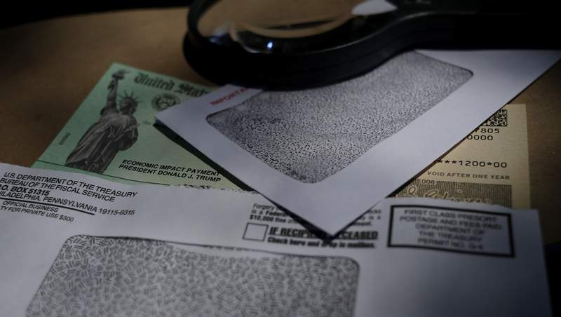 FILE- In this April 23, 2020, file photo a stimulus check issued by the IRS to help combat the adverse economic effects of the COVID-19 outbreak is shown in San Antonio.