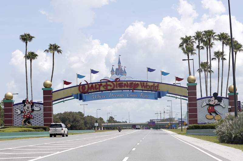 FILE - In this Thursday, July 2, 2020, file photo, cars drive under a sign greeting visitors near the entrance to Walt Disney World, in Lake Buena Vista, Fla. A new television show about the residents and caretakers at Walt Disney World's Animal Kingdom is being produced by National Geographic and will start streaming in the fall of 2020 on the Disney+. (AP Photo/John Raoux, File)