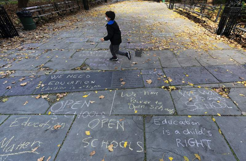 """FILE - A child runs across a sidewalk in front of New York's City Hall decorated with graffiti in favor of keeping open public schools, Thursday, Nov. 19, 2020. A Google services outage this week and potential impacts from a snowstorm in the Northeast highlight the fragile chain of connectivity that's powering widespread remote learning during the coronavirus pandemic. One Ohio school superintendent called Monday's Google outage the COVID version of a snow day."""" (AP Photo/Mark Lennihan, file)"""