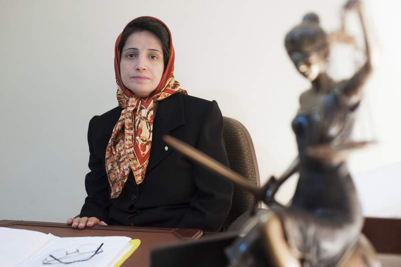 FILE - In this Nov. 1, 2008 photo, Iranian human rights lawyer Nasrin Sotoudeh, poses for a photograph in her office in Tehran, Iran.  Iran's state-run news agency says on Saturday, Nov. 7, 2020,  the leading Iranian human rights lawyer has been released from prison, a month after she was hospitalized amid a hunger-strike conducted from her cell. Sotoudeh was taken to hospital in mid-September, a month after launching her hunger strike seeking better prison conditions and the release of political prisoners amid the pandemic. (AP Photo/Arash Ashourinia)