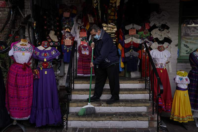 Victor Flores, 66, a third-generation owner of a gift shop, sweeps the steps of his store on Olvera Street in downtown Los Angeles, Wednesday, Dec. 16, 2020. Millions of business owners are about to get additional help as they weather the coronavirus outbreak. The Small Business Administration and the Treasury Department are reviving the Paycheck Protection Program five months after its first two rounds of funding ended. (AP Photo/Jae C. Hong, file)