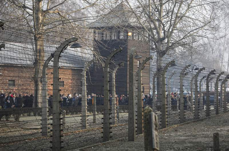 """FILE- In this file photo taken Jan. 27, 2020, people are seen arriving at the site of the Auschwitz-Birkenau Nazi German death camp, where more than 1.1 million were murdered, in Oswiecim, Poland, for observances marking 75 years since the camp's liberation by the Soviet army. Needham, Massachusetts-based TripAdvisor on Thursday, May 6, 2021, faced criticism from the camp's museum and memorial after an author posted an inappropriate review of the museum on the TripAdvisor website, stating the reviewer visited to """"test the chamber"""". The company originally declined to remove the message. (AP Photo/Czarek Sokolowski, FIle)"""