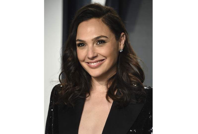 FILE - Gal Gadot arrives at the Vanity Fair Oscar Party on Sunday, Feb. 9, 2020, in Beverly Hills, Calif.  Gadot is using her Hollywood star power to spotlight remarkable women from around the world. The Wonder Woman actor is host and executive producer of a new documentary series National Geographic Presents IMPACT with Gal Gadot, premiering Monday, April 26. (Photo by Evan Agostini/Invision/AP, File)