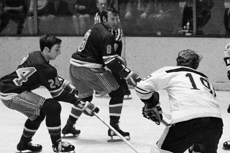 FILE - In this April 16, 1970, file photo, New York Rangers' Bob Nevin (8), center, plays during an NHL hockey game against the Boston Bruins in New York. Nevin, a fan favorite who won two Stanley Cups with the Toronto Maple Leafs before a successful run as captain of the New York Rangers, has died. He was 82. The NHL said he died early Monday, Sept. 21, 2020, but did not give a cause. (AP Photo/File)
