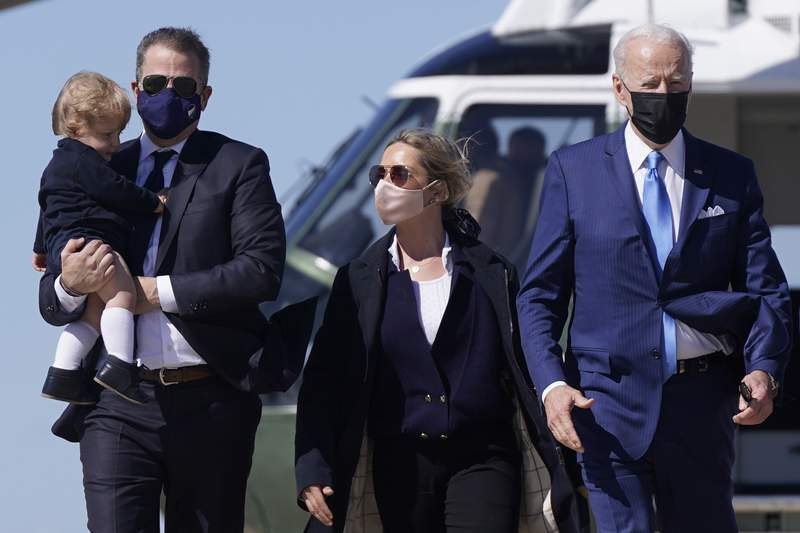 FILE - In this March 26, 2021, file photo President Joe Biden walks with his son Hunter Biden, second from left, as Hunter carries his son Beau and walks next to his wife Melissa Cohen, center, before boarding Air Force One at Andrews Air Force Base, Md. The White House has established an arrangement that would allow President Joe Bidens son Hunter to sell his artwork for tens of thousands of dollars without knowing the identity of the purchaser, an agreement established in attempt to avoid any potential ethical concerns surrounding his sales. (AP Photo/Patrick Semansky, File)