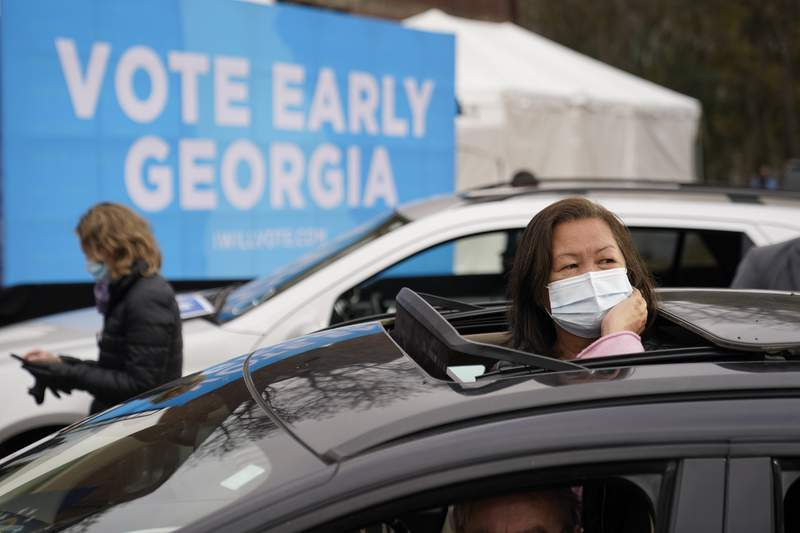 Attendees wait for President-elect Joe Biden to be introduced at a drive-in rally for Georgia Democratic candidates for U.S. Senate Raphael Warnock and Jon Ossoff, Tuesday, Dec. 15, 2020, in Atlanta. (AP Photo/Patrick Semansky)