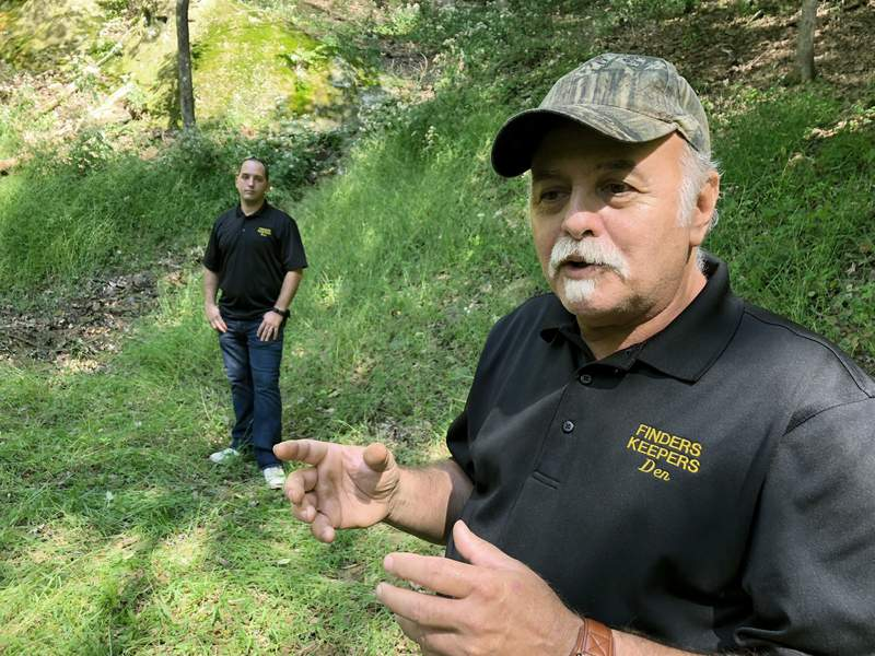 FILE-This Sept. 20, 2018 file photo, Dennis Parada, right, and his son Kem Parada stand at the site of the FBI's dig for Civil War-era gold in Dents Run, Pennsylvania. Government emails released under court order show that FBI agents were looking for gold when they excavated Dent's Run in 2018, though the FBI says that nothing was found. (AP Photo/Michael Rubinkam, File)