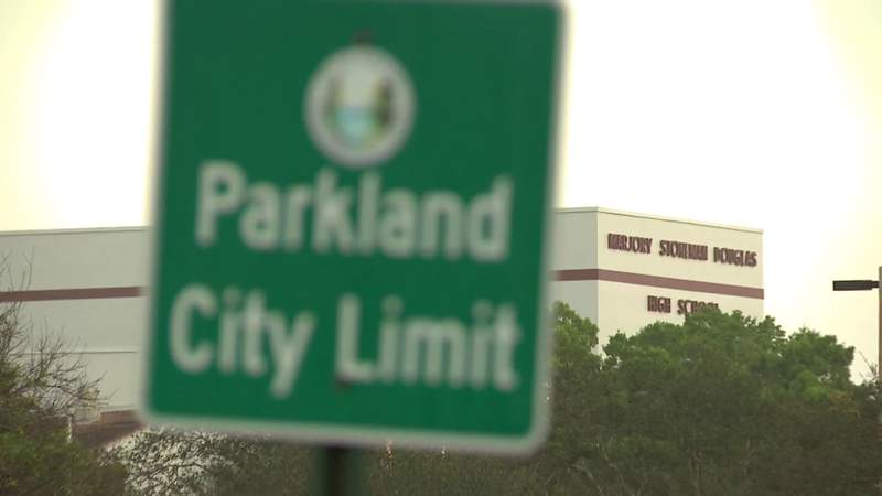 A Parkland city limit sign stands in the foreground not far from Marjory Stoneman Douglas High School on the two-year anniversary of the 2018 mass shooting, Feb. 14, 2020, in Parkland, Florida.