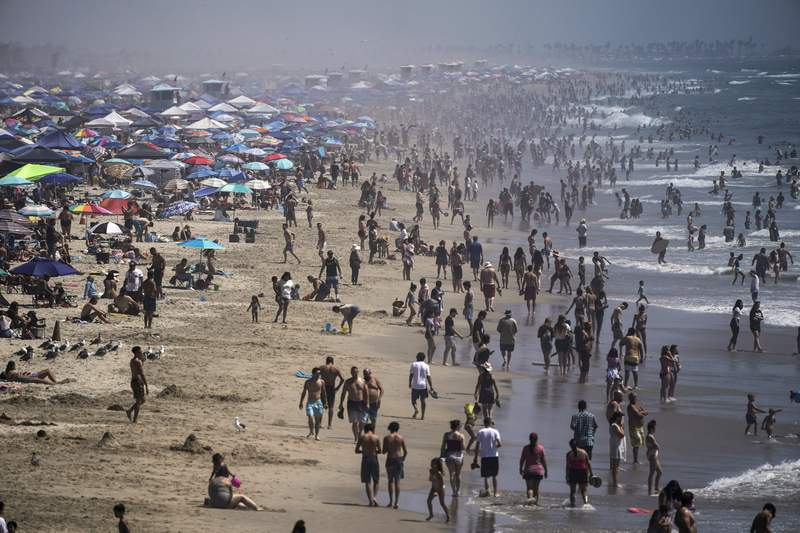 FILE - In this Saturday, Sept. 5, 2020 file photo, people crowd the beach in Huntington Beach, Calif., as the state swelters under a heat wave. On Wednesday, Oct. 14, 2020, the U.S. National Oceanic and Atmospheric Administration said the Earth reached a record hot September, saying that theres nearly a two-to-one chance that 2020 will end up as the globes hottest year on record. (AP Photo/Jae C. Hong)