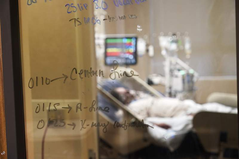 FILE - In this Wednesday, Aug. 18, 2021 file photo, Medical notations are written on a window of a COVID-19 patient's room in an intensive care unit at the Willis-Knighton Medical Center in Shreveport, La.  Louisiana hospitals already packed with patients from the latest coronavirus surge are now bracing for a powerful Category 4 hurricane, which is expected to crash ashore Sunday, Aug. 28, 2021. (AP Photo/Gerald Herbert, File)