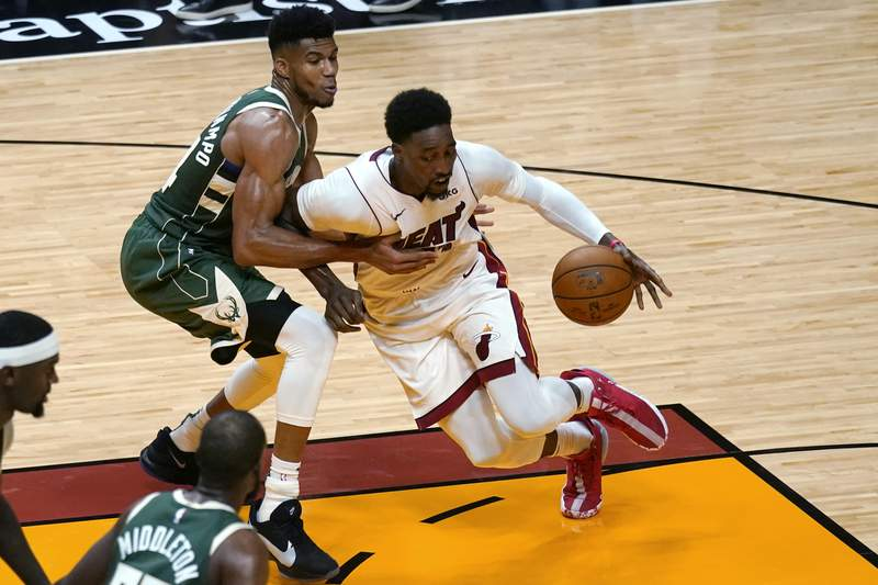 Miami Heat center Bam Adebayo, right, controls the ball as Milwaukee Bucks forward Giannis Antetokounmpo, back left, defends during the first half of an NBA basketball game Wednesday, Dec. 30, 2020, in Miami. (AP Photo/Lynne Sladky)