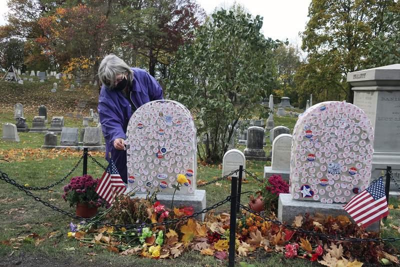 """Gavin Neville, 72, places an """"I Voted"""" sticker on the grave of women's rights advocate Susan B. Anthony in Rochester, New York, on Monday, Nov. 2, 2020. The cemetery has put a plastic cover on the headstone so voters can place stickers on it without damaging the headstone."""