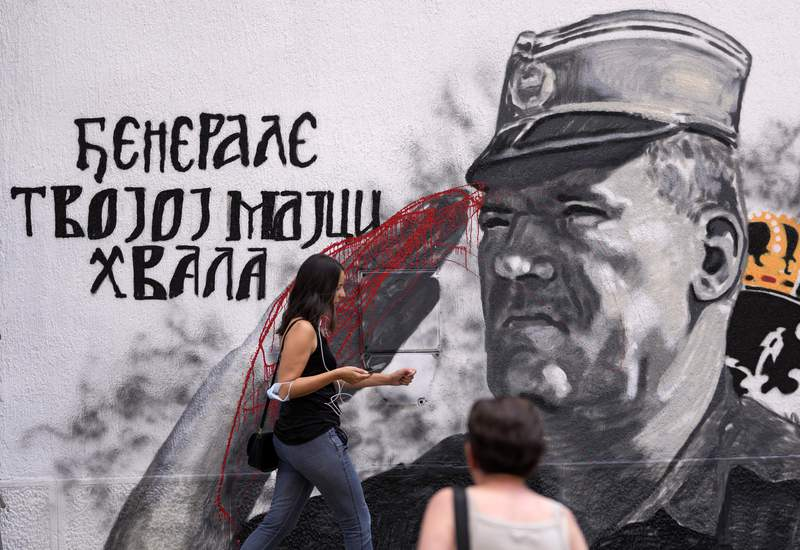People walk by a mural of former Bosnian Serb military chief Ratko Mladic vandalized with red paint in Belgrade, Serbia, Saturday, July 24, 2021. The Bosnian Serb wartime political leader Radovan Karadzic and his military commander Ratko Mladic were both convicted of genocide in Srebrenica by a special U.N. war crimes tribunal in The Hague. Valentin Inzko, the outgoing head of Bosnia's Office of the High Representative, or OHR, imposed changes Friday to the country's criminal code, introducing prison sentences of up to five years for genocide denial and for the glorification of war criminals. (AP Photo/Darko Vojinovic)