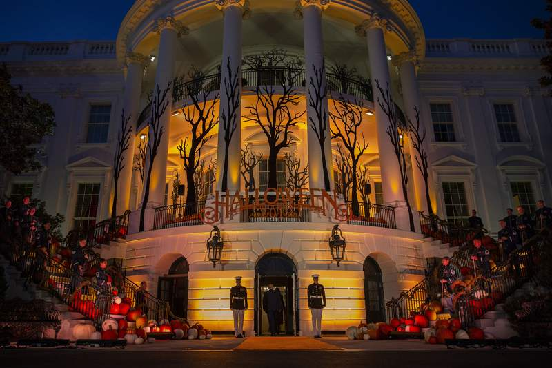FILE - In this Oct. 28, 2019 file photo, President Donald Trump and first lady Melania Trump depart after giving candy to children during a Halloween trick-or-treat event on the South Lawn of the White House in Washington, which is decorated for Halloween.  Melania Trump announced Friday that ghosts and goblins are welcome to trick or treat at the White House on Sunday during a Halloween event that has been rejiggered to include coronavirus precautions.    President Donald Trump and the first lady  both recently recovered from COVID-19, the disease brought on by the coronavirus  will welcome guests. (AP Photo/Alex Brandon)