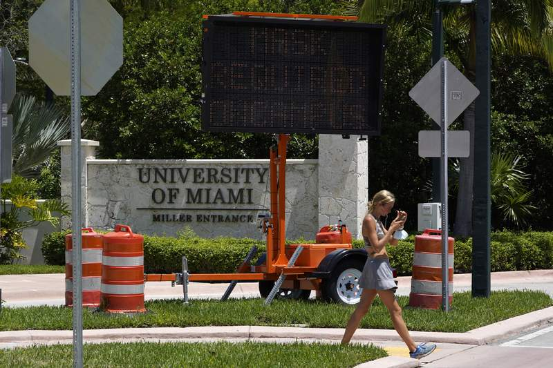 In this Aug. 25, 2020, file photo, a pedestrian walks past an entrance to the University of Miami in Coral Gables. (AP Photo/Wilfredo Lee, File)