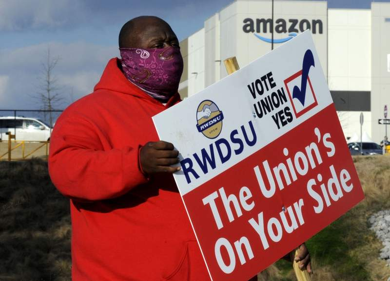 FILE - In this Tuesday, Feb. 9, 2021 file photo ,Michael Foster of the Retail, Wholesale and Department Store Union holds a sign outside an Amazon facility where labor is trying to organize workers in Bessemer, Ala.  Organizers trying to form the first union at an Amazon warehouse are getting support from another big name: Black Lives Matter. The group plans to hold an event Saturday, March 13, 2021 near the warehouse in Bessemer, Alabama, making it the latest high-profile supporter of the union push, which is the biggest in Amazon's nearly 30-year history. (AP Photo/Jay Reeves, File)