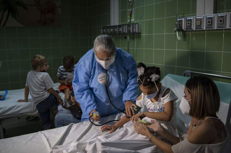 A nurse takes a girl's blood pressure after giving her a dose of the Cuban-made Soberana-02 vaccine for COVID-19 in Havana, Cuba, Tuesday, Aug. 24, 2021. (AP Photo/Ramon Espinosa)