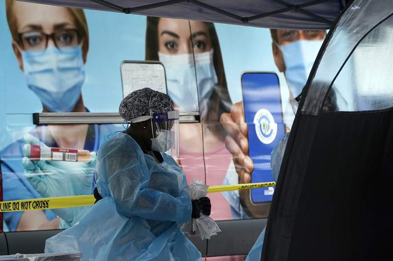 A health care employee works at a walk-up COVID-19 testing site in Miami.(AP Photo/Lynne Sladky)
