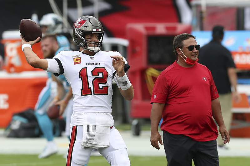 Tampa Bay Buccaneers quarterback Tom Brady (12) throws a pass as quarterback's coach Clyde Christensen looks on before an NFL football game against the Carolina Panthers Sunday, Sept. 20, 2020, in Tampa, Fla. (AP Photo/Mark LoMoglio)